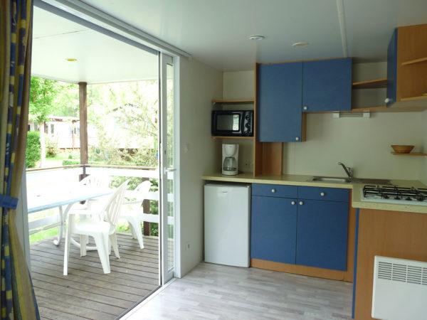 Vue cuisine et terrasse en bois mobil'home pour 5 personnes