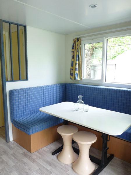 Banquette convertible et espace repas intérieur du mobil'home pour 5 personnes