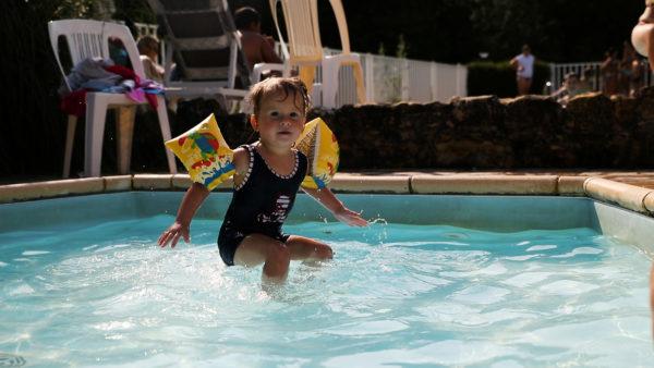 Enfant sautant dans la piscine chauffée