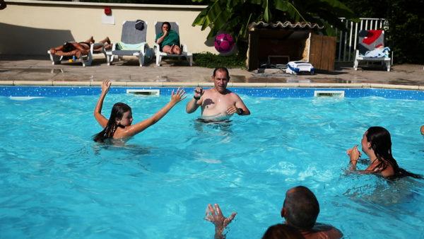 Jeux aquatiques d'une famille à la piscine du camping