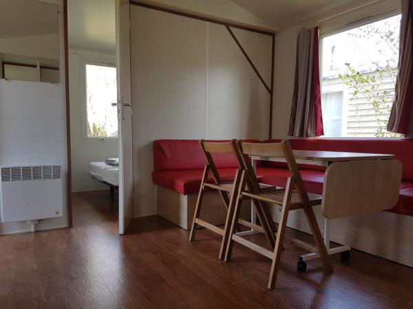Banquette convertible et espace repas intérieur du mobil'home pour 6 personnes