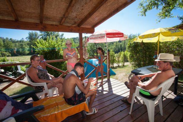 Moment en famille sous la pergola d'un mobil'home du camping La Lénotte