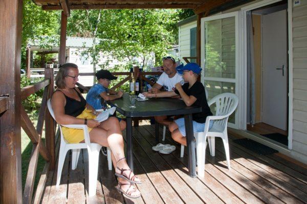 Moment famille sur la terrasse en bois d'un mobil'home 6 personnes